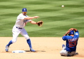 Mark Ellis of the Los Angeles Dodgers makes a throw to first base in front of a sliding Welington Castillo of the Chicago Cubs during the fifth...