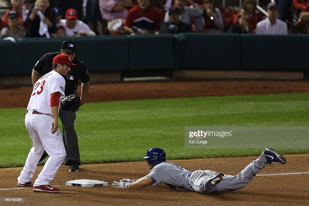 Mark Ellis #14 of the Los Angeles Dodgers slides into third on a triple in the 10th inning against the St. Louis Cardinals during Game One of the National League Championship Series at Busch Stadium on October 11, 2013 in St Louis, Missouri.