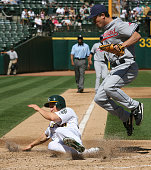 Mark Ellis of the Oakland Athletics slides home safely scoring on a wild pitch as Cleveland Indians pitcher Tomo Ohka waits for the late throw during...