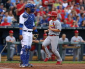 Mark Ellis of the St Louis Cardinals scores against Salvador Perez of the Kansas City Royals on a Matt Carpenter single in the second inning against...