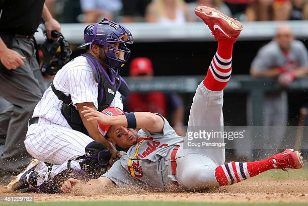 Mark Ellis of the St Louis Cardinals slides home to score against catcher Wilin Rosario of the Colorado Rockies on a pinch hit double by Daniel...