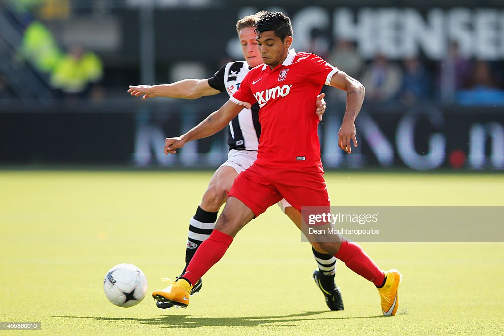 Mark Engberink (L) of Heracles tackles Jesus Corona of Twente during the Dutch Eredivisie match between Heracles Almelo and FC Twente at Polman Stadion on September 21, 2014 in Almelo, Netherlands.