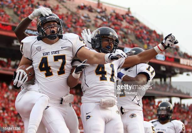 Mark Fackler celebrates a touchdown with teammates Zack Hitchens and Norman Wolfe Jr #11 of the Kent State Golden Flashes against the Rutgers Scarlet...
