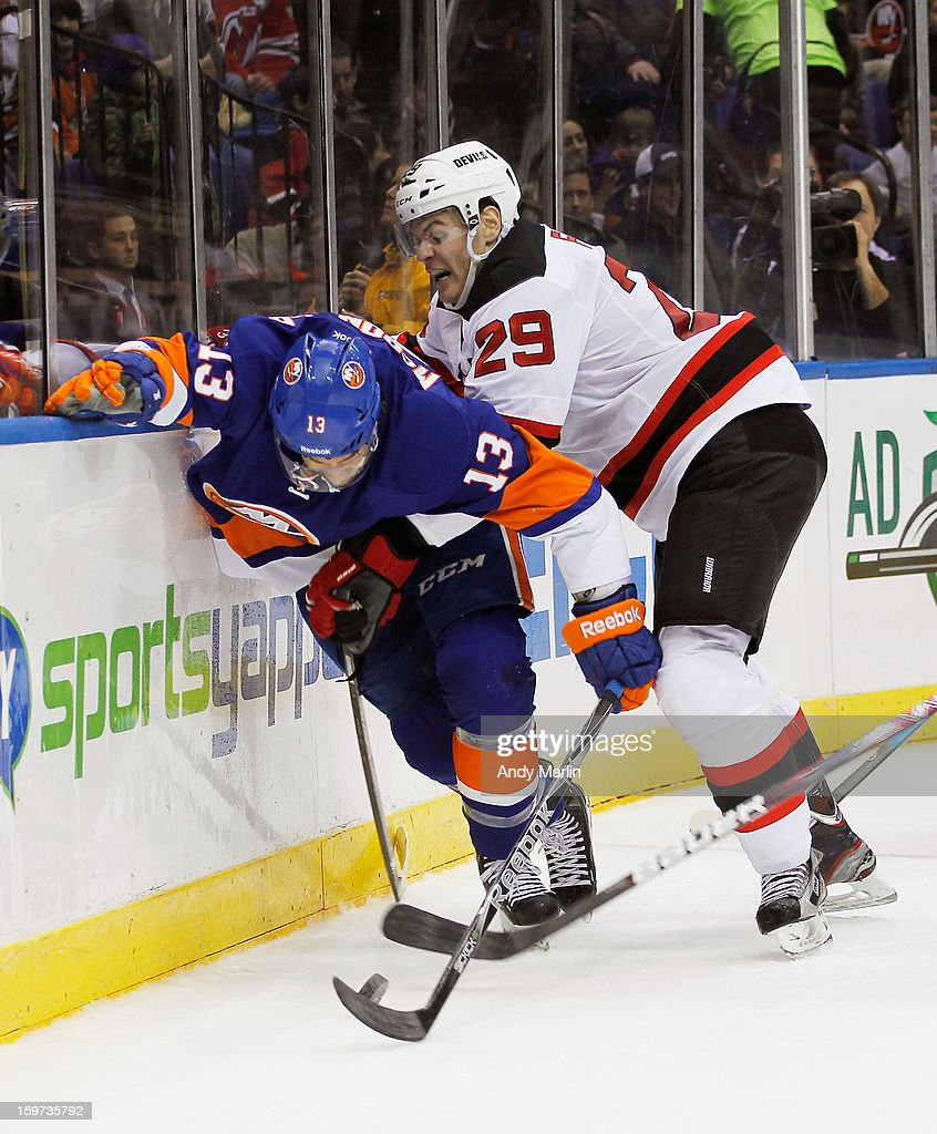 Mark Fayne #29 of the New Jersey Devils and Colin McDonald #13 of the New York Islanders battle along the boards for a loose puck during the Islanders home opener at the Nassau Coliseum on January 19, 2013 in Uniondale, New York.