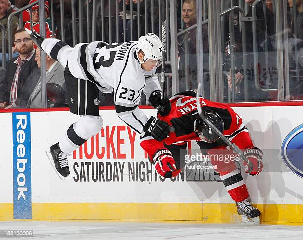 Mark Fayne of the New Jersey Devils sends Dustin Brown of the Los Angeles Kings flying on a check in the first period of an NHL hockey game at...