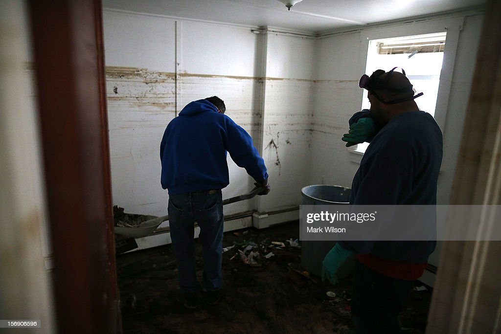 Mark Fischetti (R), and Mel Firetto shovel sand and trash from a home damaged by Superstorm Sandy, on November 24, 2012 in Seaside Heights, New Jersey. New Jersey Gov. Christie estimated that Superstorm Sandy cost New Jersey $29.4 billion in damage and economic losses.