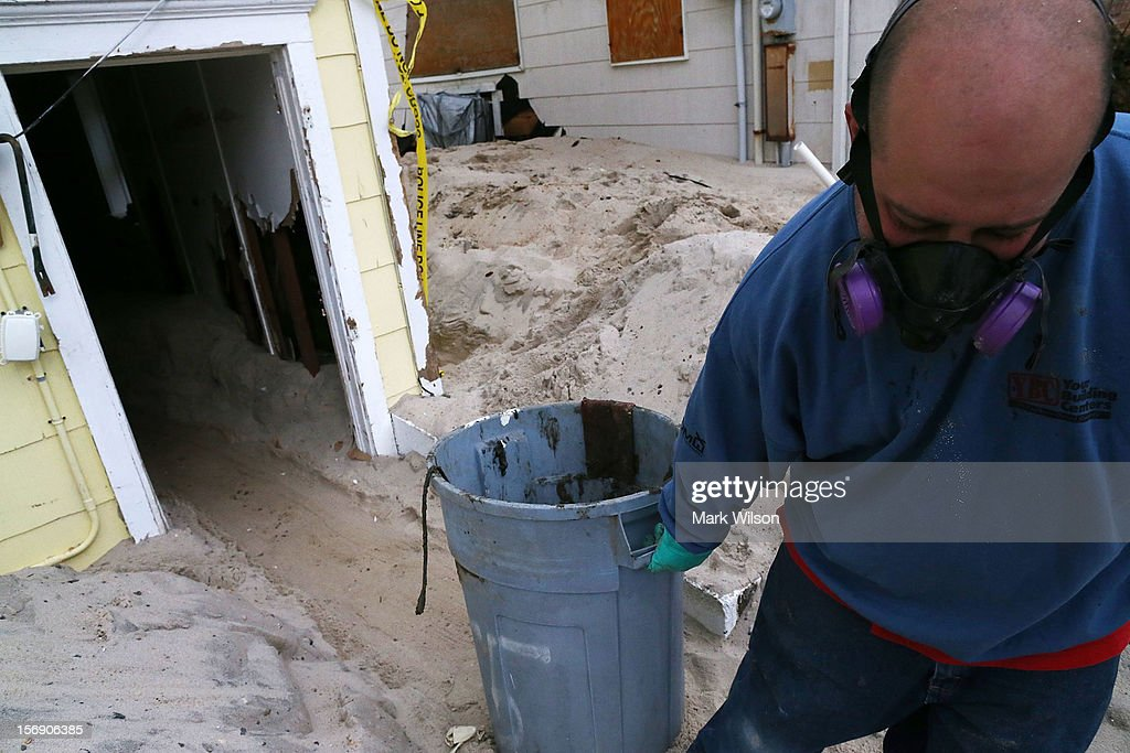 Mark Fischetti pulls a barrel of trash out of a home damaged by Superstorm Sandy, on November 24, 2012 in Seaside Heights, New Jersey. New Jersey Gov. Christie estimated that Superstorm Sandy will cost New Jersey $29.4 billion in damage and economic losses.