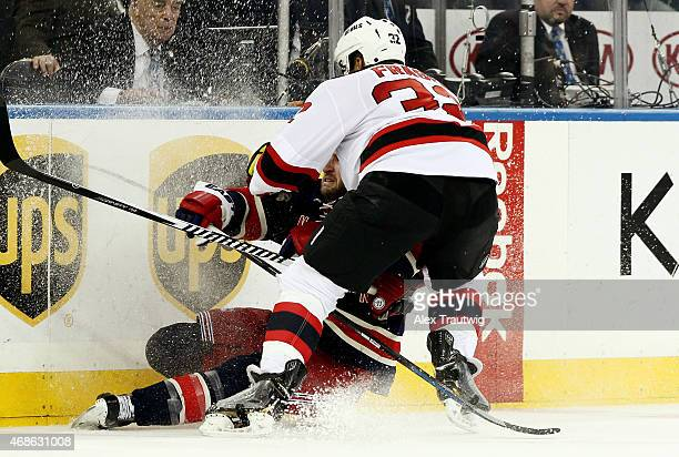 Mark Fraser of the New Jersey Devils checks Tanner Glass of the New York Rangers during a game at Madison Square Garden on April 4 2015 in New York...