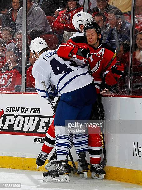 Mark Fraser of the Toronto Maple Leafs checks Patrik Elias of the New Jersey Devils during the game at the Prudential Center on April 6 2013 in...
