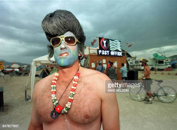 Mark from Las Vegas dressed as a blue faced Elvis Presley sneers near the Burning Man Post Office 05 September at the Burning Man Festival in the...