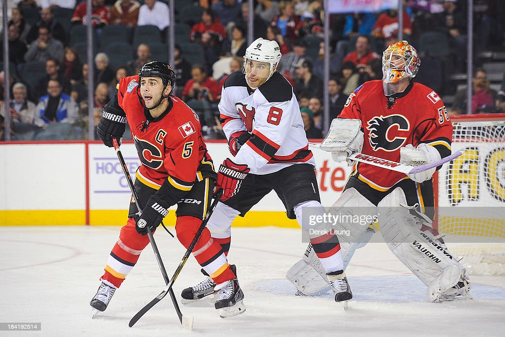 Mark Giordano #5 and Joey MacDonald #35 of the Calgary Flames defend against Dainius Zubrus #8 of the New Jersey Devils during an NHL game at Scotiabank Saddledome on October 11, 2013 in Calgary, Alberta, Canada. The Calgary Flames defeated the New Jersey Devils 3-2.