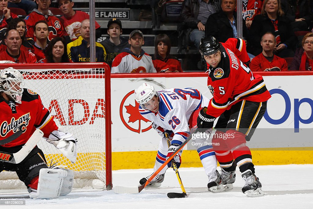Mark Giordano #5 and Karri Ramo #31 of the Calgary Flames defend the net in a game against Martin St. Louis #26 of the New York Rangers at Scotiabank Saddledome on March 28, 2014 in Calgary, Alberta, Canada.