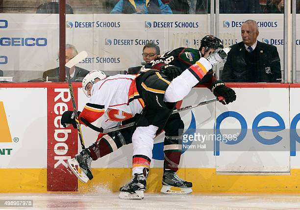 Mark Giordano of the Calgary Flames and Michael Stone of the Arizona Coyotes collide along the boards during the first period at Gila River Arena on...