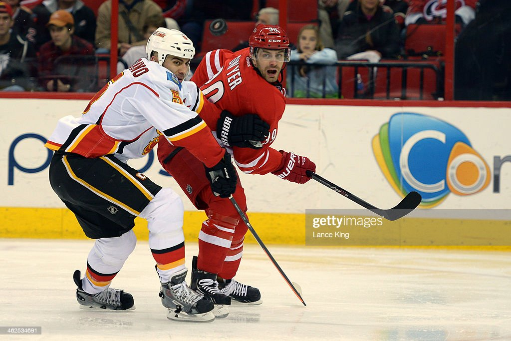 <a gi-track='captionPersonalityLinkClicked' href=/galleries/search?phrase=Mark+Giordano&family=editorial&specificpeople=696867 ng-click='$event.stopPropagation()'>Mark Giordano</a> #5 of the Calgary Flames and Patrick Dwyer #39 of the Carolina Hurricanes battle for the puck at PNC Arena on January 13, 2014 in Raleigh, North Carolina. The Flames defeated the Hurricanes 2-0.