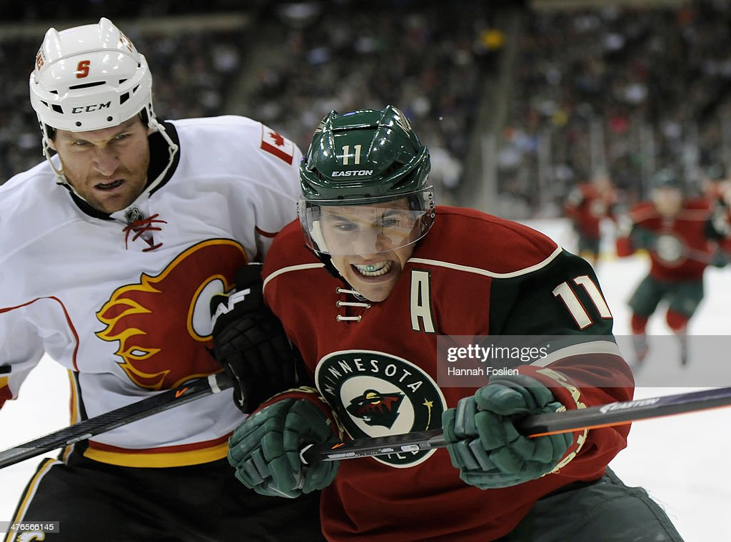 Mark Giordano #5 of the Calgary Flames and Zach Parise #11 of the Minnesota Wild skate after the puck during the second period of the game on March 3, 2014 at Xcel Energy Center in St Paul, Minnesota.