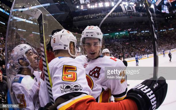 Mark Giordano of the Calgary Flames celebrates his goal against the Toronto Maple Leafs with teammates Sean Monahan and Johnny Gaudreau during the...