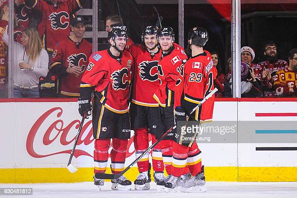 Mark Giordano of the Calgary Flames celebrates with his teammates after scoring his team's third goal against the Vancouver Canucks during an NHL...