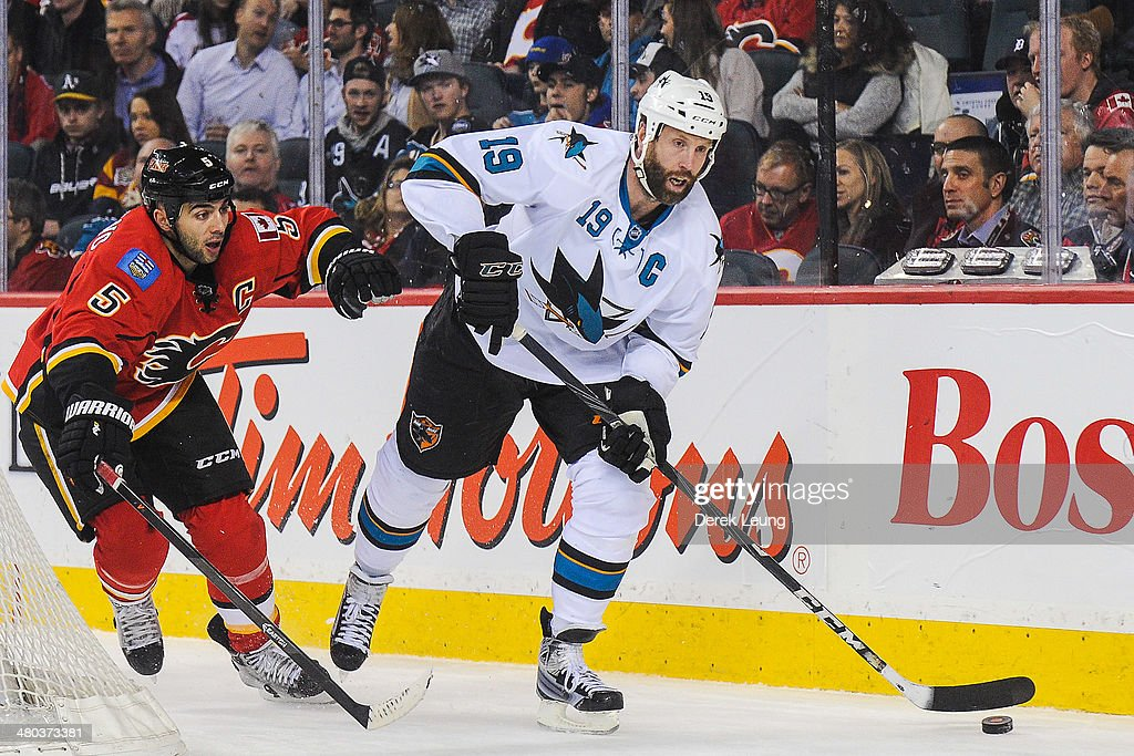 Mark Giordano #5 of the Calgary Flames chases Joe Thornton #19 of the San Jose Sharks during an NHL game at Scotiabank Saddledome on March 24, 2014 in Calgary, Alberta, Canada.