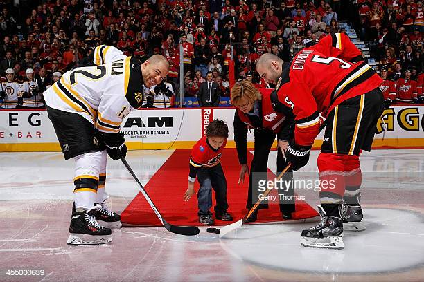 Mark Giordano of the Calgary Flames faces off against Jarome Iginla of the Boston Bruins in a ceremonial puck drop at Scotiabank Saddledome on...