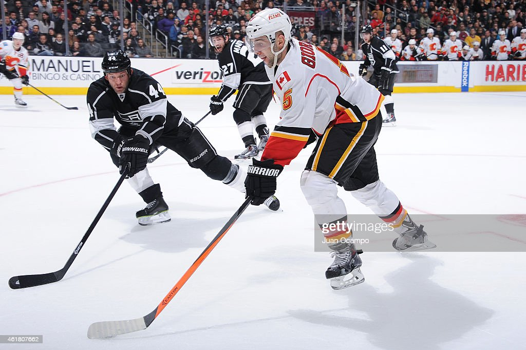 Mark Giordano #5 of the Calgary Flames handles the puck against Robyn Regehr #44 of the Los Angeles Kings at STAPLES Center on January 19, 2015 in Los Angeles, California.