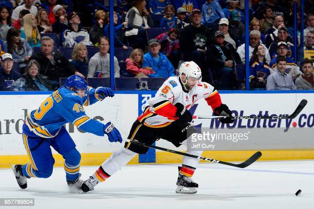Mark Giordano of the Calgary Flames handles the puck as Ivan Barbashev of the St Louis Blues defends on March 25 2017 at Scottrade Center in St Louis...