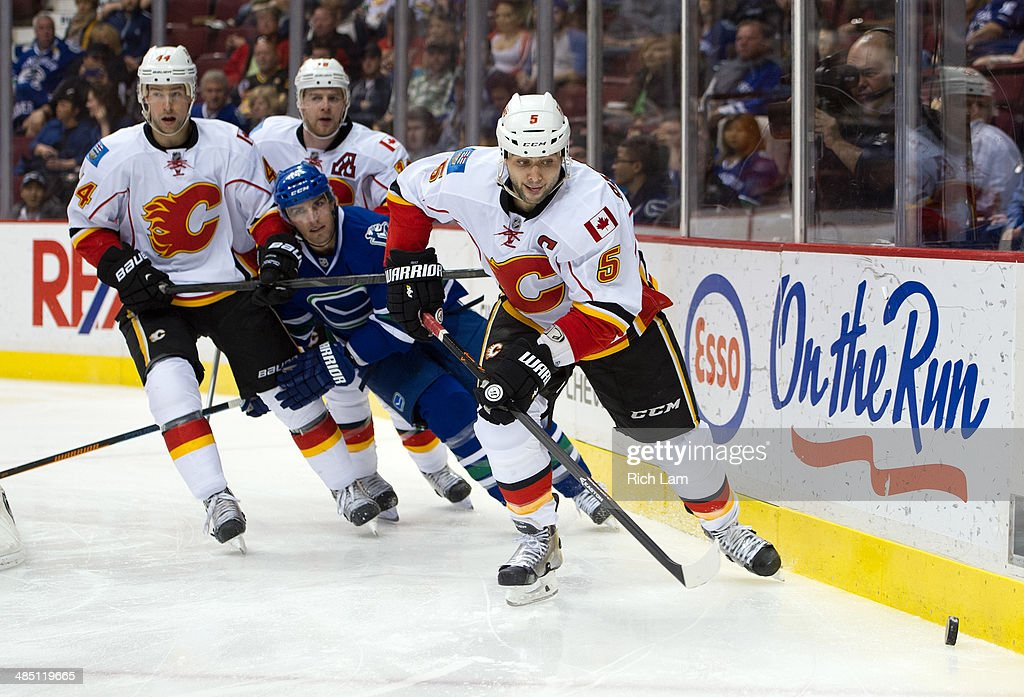 Mark Giordano #5 of the Calgary Flames picks up the loose puck while Chris Butler #44 and Matt Stajan #18 hold up Alexandre Burrows #14 of the Vancouver Canucks during NHL action against the Vancouver Canucks on April 13, 2014 at Rogers Arena in Vancouver, British Columbia, Canada.