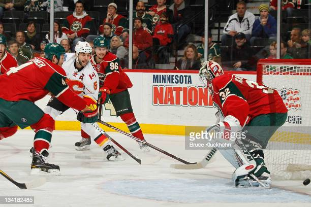 Mark Giordano of the Calgary Flames scores a goal against goaltender Nicklas Backstrom of the Minnesota Wild during the game at the Xcel Energy...