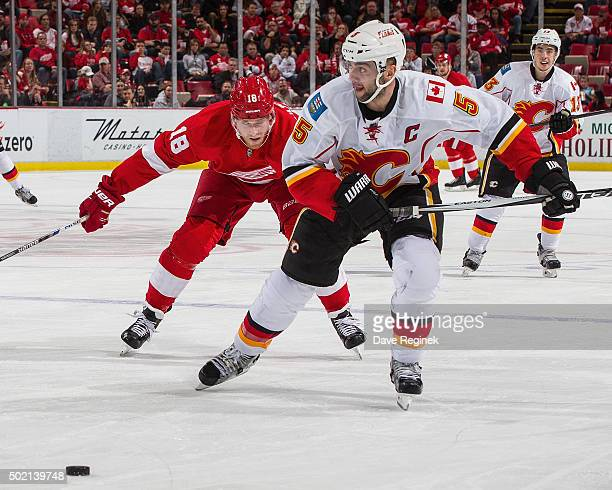 Mark Giordano of the Calgary Flames skates after a loose puck in front of Joakim Andersson of the Detroit Red Wings during an NHL game at Joe Louis...