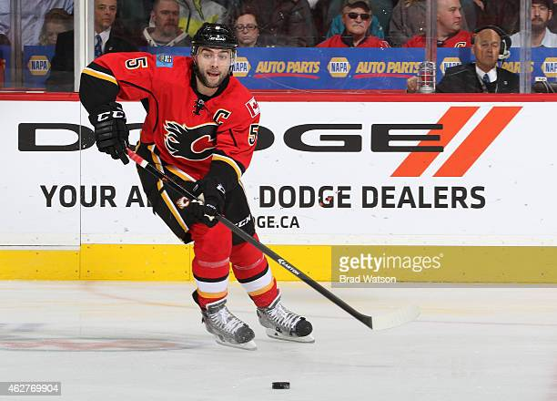 Mark Giordano of the Calgary Flames skates the puck up ice against the San Jose Sharks at Scotiabank Saddledome on February 4 2015 in Calgary Alberta...
