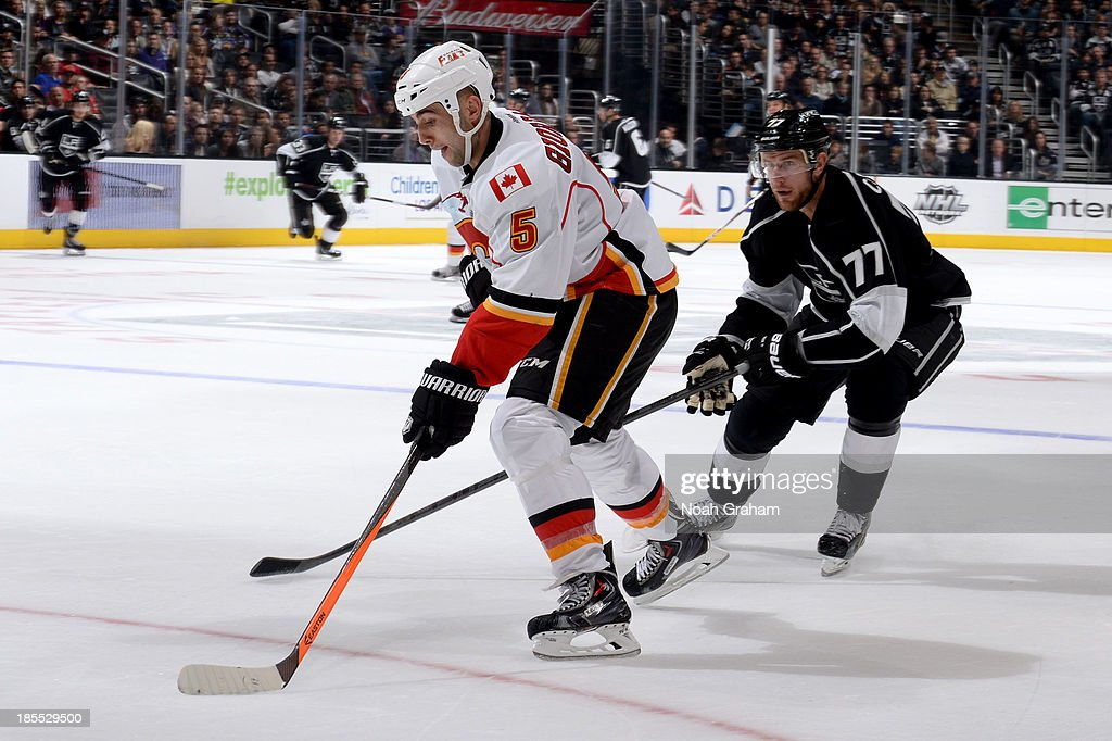 <a gi-track='captionPersonalityLinkClicked' href=/galleries/search?phrase=Mark+Giordano&family=editorial&specificpeople=696867 ng-click='$event.stopPropagation()'>Mark Giordano</a> #5 of the Calgary Flames skates with the puck against <a gi-track='captionPersonalityLinkClicked' href=/galleries/search?phrase=Jeff+Carter&family=editorial&specificpeople=227320 ng-click='$event.stopPropagation()'>Jeff Carter</a> #77 of the Los Angeles Kings at Staples Center on October 21, 2013 in Los Angeles, California.