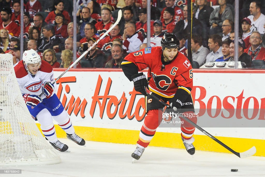 <a gi-track='captionPersonalityLinkClicked' href=/galleries/search?phrase=Mark+Giordano&family=editorial&specificpeople=696867 ng-click='$event.stopPropagation()'>Mark Giordano</a> #5 of the Calgary Flames skates with the puck as <a gi-track='captionPersonalityLinkClicked' href=/galleries/search?phrase=Alex+Galchenyuk&family=editorial&specificpeople=7419137 ng-click='$event.stopPropagation()'>Alex Galchenyuk</a> #27 of the Montreal Canadiens chases him during an NHL game at Scotiabank Saddledome on October 9, 2013 in Calgary, Alberta, Canada.