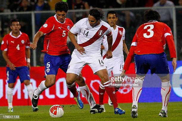Mark Gonzalez from Chile fights for the ball with Claudio Pizarro from Peru during the match between Chile and Peru as part of the first round of the...