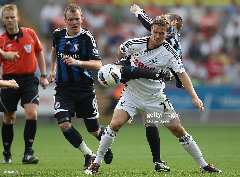 Mark Gower of Swansea City is challenged by Rory Delap of Stoke City as Glenn Whelan (L) looks on during the Barclays Premier League match between Swansea City and Stoke City at the Liberty Stadium on October 2, 2011 in Swansea, Wales.