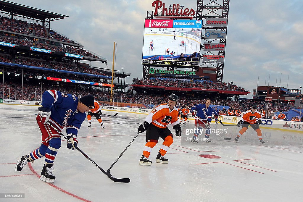Mark Howe #2 of the Philadelphia Flyers defends against Pat Hickey #16 of the New York Rangers during the 2012 Bridgestone NHL Winter Classic Alumni Game on December 31, 2011 at Citizens Bank Park in Philadelphia, Pennsylvania.
