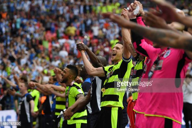 Mark Hudson of Huddersfield Town celebrates promotion to the Premier League with his Huddersield Town team mates after the Sky Bet Championship play...