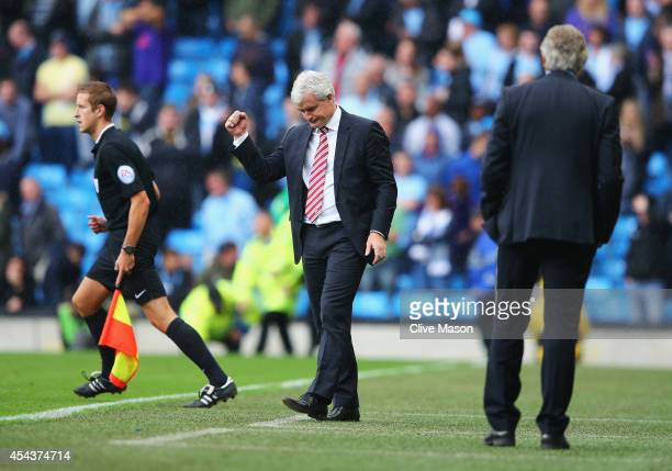 Mark Hughes manager of Stoke City celebrates victory with Manuel Pellegrini manager of Manchester City after the Barclays Premier League match...
