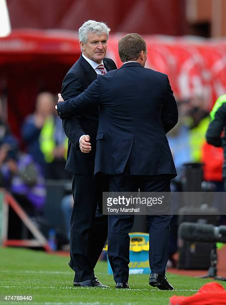 Mark Hughes Manager of Stoke Cityshakes hands with Brendan Rodgers Manager of Liverpool at the end of the Barclays Premier League match between Stoke...