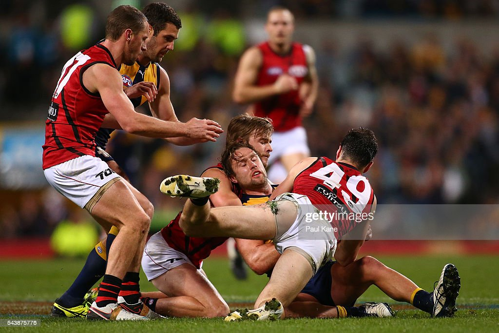 Mark Hutchings of the Eagles gets tackled by Martin Gleeson and Matt Dea of the Bombers during the round 15 AFL match between the West Coast Eagles and the Essendon Bombers at Domain Stadium on June 30, 2016 in Perth, Australia.
