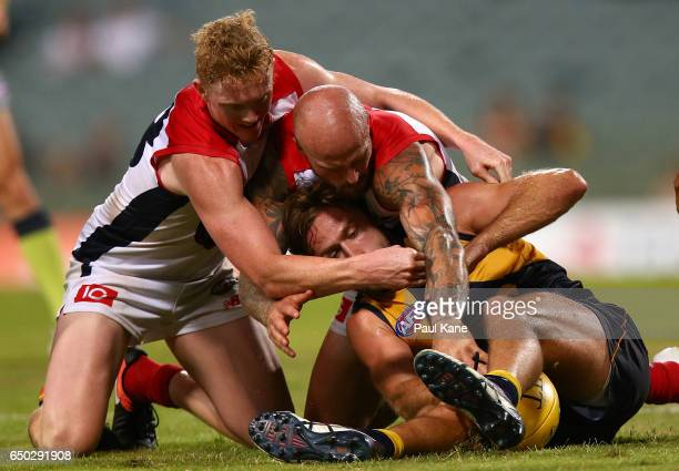 Mark Hutchings of the Eagles gets tackled by Nathan Jones and Clayton Oliver of the Demons during the JLT Community Series AFL match between the West...