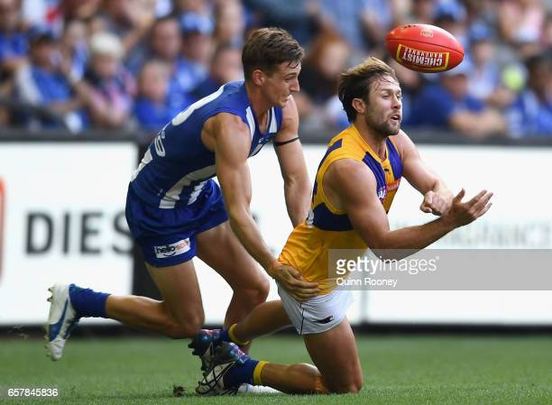Mark Hutchings of the Eagles handballs whilst being tackled Shaun Atley of the Kangaroos during the round one AFL match between the North Melbourne...
