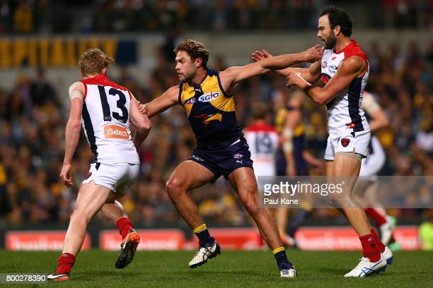 Mark Hutchings of the Eagles is double teamed by Clayton Oliver and Jordan Lewis of the Demons at a kick out during the round 14 AFL match between...