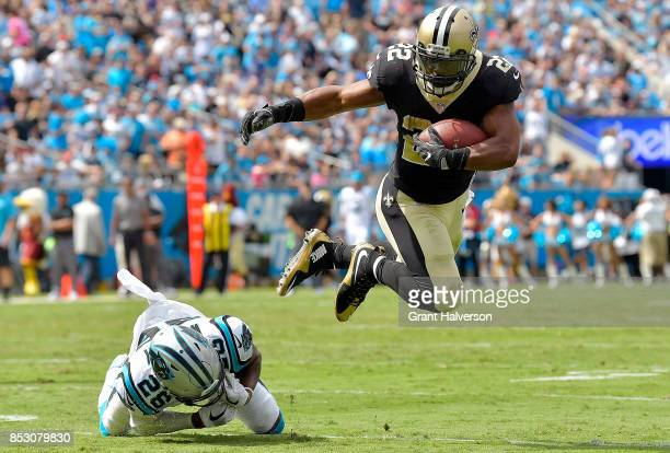 Mark Ingram of the New Orleans Saints hurdles Daryl Worley of the Carolina Panthers during their game at Bank of America Stadium on September 24 2017...