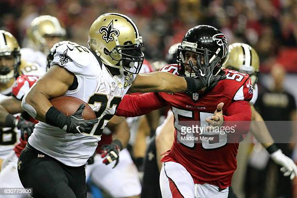 Mark Ingram of the New Orleans Saints stiff arms Paul Worrilow of the Atlanta Falcons during the first half at the Georgia Dome on January 1 2017 in...