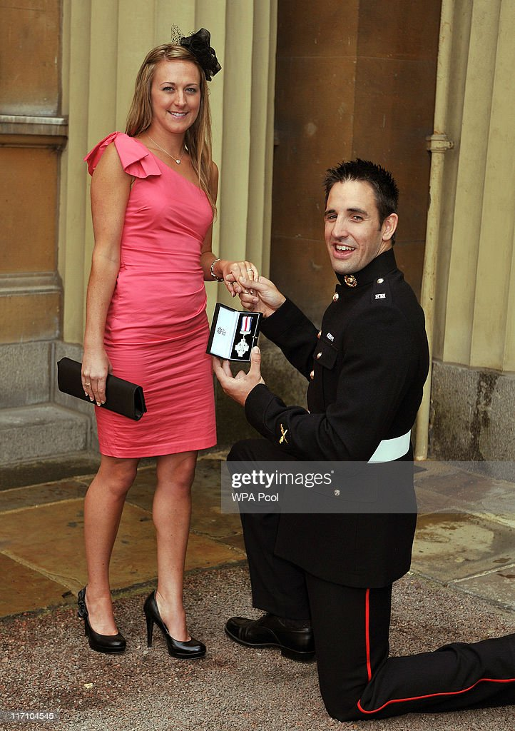 Mark Jackson of the Royal Marines proposes to his girlfriend Rebecca Daniel, as he holds his Conspicuous Gallantry Cross after it was presented to him by the Prince of Wales, at the Investiture Ceremony on June 23, 2011 at Buckingham Palace, London.