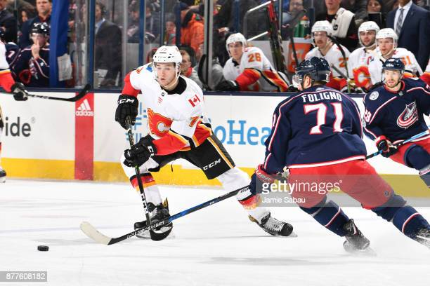 Mark Jankowski of the Calgary Flames and Nick Foligno of the Columbus Blue Jackets skate after a loose puck during the second period of a game on...