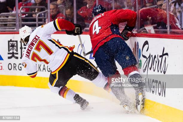 Mark Jankowski of the Calgary Flames and Taylor Chorney of the Washington Capitals collide in the second period at Capital One Arena on November 20...