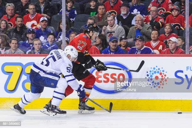 Mark Jankowski of the Calgary Flames chases the puck against Andreas Borgman of the Toronto Maple Leafs during an NHL game at Scotiabank Saddledome...