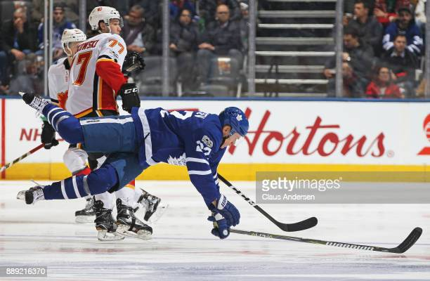 Mark Jankowski of the Calgary Flames knocks Nikita Zaitsev of the Toronto Maple Leafs to the ice during an NHL game at the Air Canada Centre on...