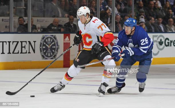 Mark Jankowski of the Calgary Flames skates away from a checking Connor Brown of the Toronto Maple Leafs during an NHL game at the Air Canada Centre...