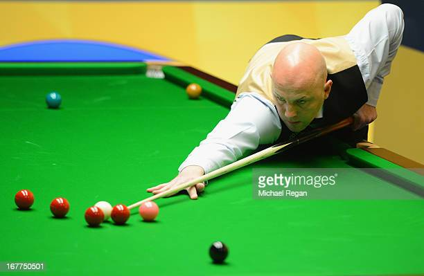 Mark King of England plays a shot in his match against Ding Junhui of China during the Betfair World Snooker Championship at the Crucible Theatre on...